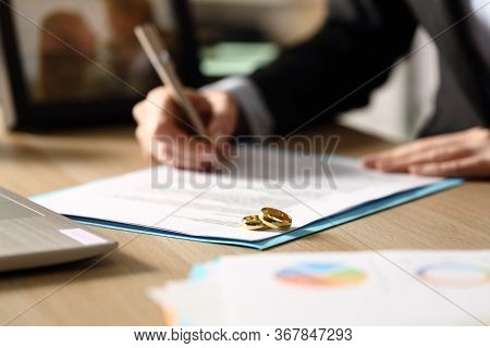 Close Up Of Freelance Woman Hands Signs Divorce Papers Sitting On A Desk At Homeoffice At Night