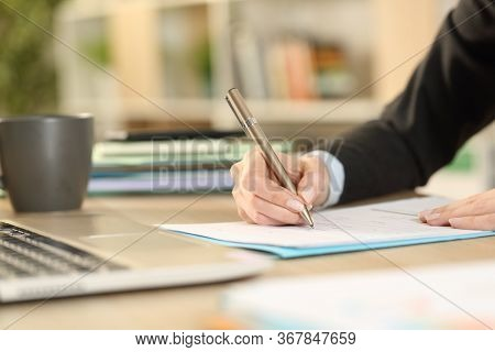 Close Up Of Freelance Woman Hands Filling Out Form Document Sitting On A Desk At Homeoffice
