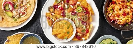 Mexican Food, A Flat Lay Panorama On A Dark Background. Nachos, Tacos, Shrimps, Shot From The Top