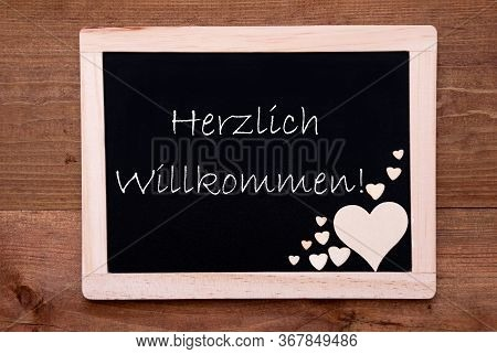 Balckboard With Wooden Heart Decoration, Text Willkommen Means Welcome