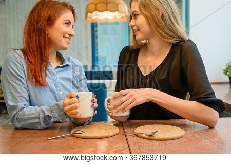 Lesbian Couple Of Women On A Date In A Cafe. Two Happy Girlfriends Drink Coffee And Chat In A Bistro