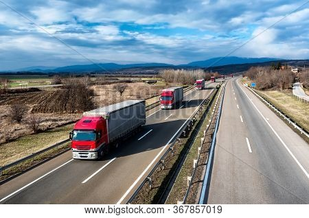 Fleet Of Red Trucks In Line As A Convoy At A Rural Countryside Highway Under A Beautiful Blue Sky