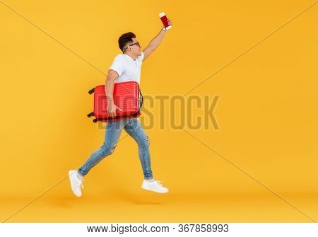 Side View Of Young Man With Suitcase Leaping Up And Taking Selfie Against Yellow Backdrop While Gett
