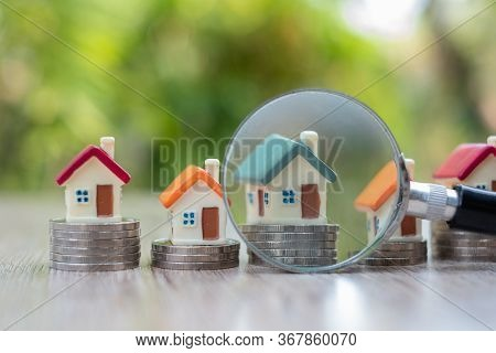 A Magnifying Glass Placed Near The House Model Placed On A Pile Of Coins Search For Houses, Investme