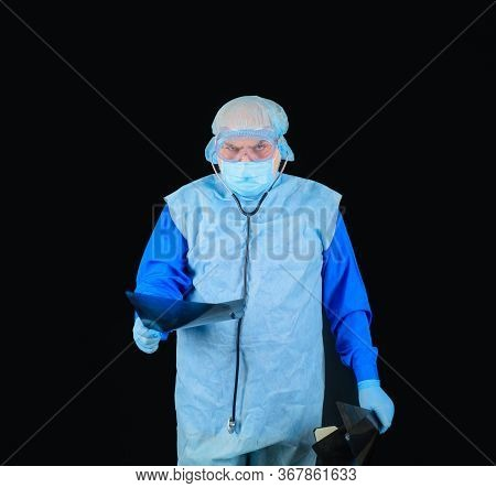 Male Doctor With X-ray. Male Doctor In Protective Suit Looking At X-ray. Radiologist Holds Patients