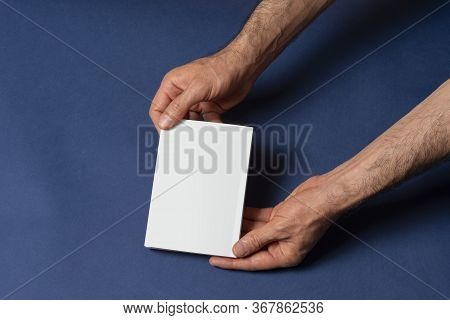 Male Hands Holding A Closed Story Book-catalog With Blank Cover On Blue Background, Mock-up Series T
