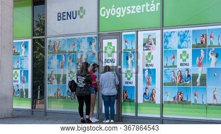 Gyor Hungary 05 22 2020: Young Girls Buy A Medical Protective Mask Against Coronavirus In A Benu Pha