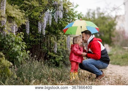 Beautiful Young Family, Dad And Little Daughter, Together Under An Umbrella, In The City On A Rainy