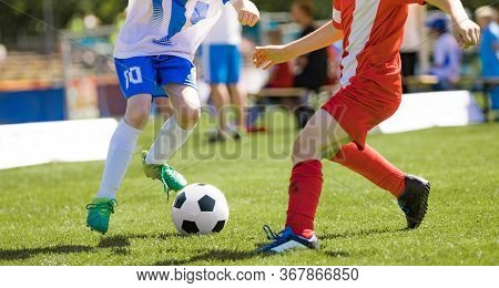 Two Junior Level Soccer Players Running And Kicking A Soccer Ball. Male Footballers In Dribbling Due