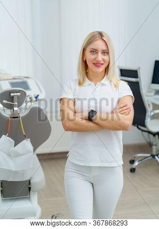 Portrait Of A Beautiful Woman Dentist Looking At Camera In A Dentist Office. Stomatologist In White