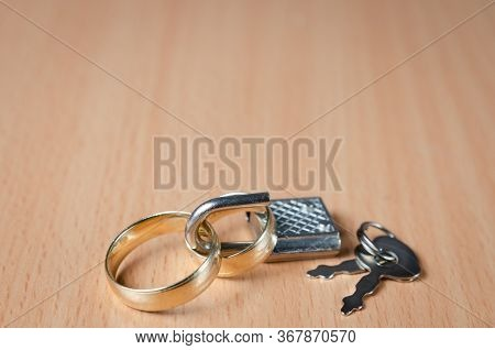 Close Up View Of  Two Wedding Rings Closed With A Padlock Representing A Concept Of United Marriage