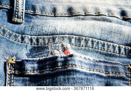 Concept Regarding   Injectable  Drugs  Addiction   . Close-up Srynge  In   Back  Poket .