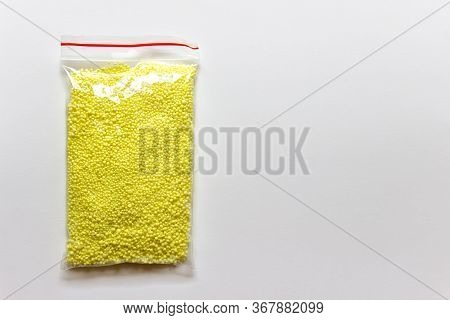 Granules Of Yellow Sulfur Chemical Element In A Plastic Bag On White Background. Photo With Copy Bla