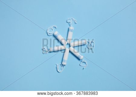 White Sanitary Hygienic Cotton Tampons On Blue Background. Feminine Hygiene Products. Top View