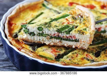 Close-up Of Quiche With Salmon Asparagus Cheese Filling Cut In Slices In A Baking Dish On An Old Woo