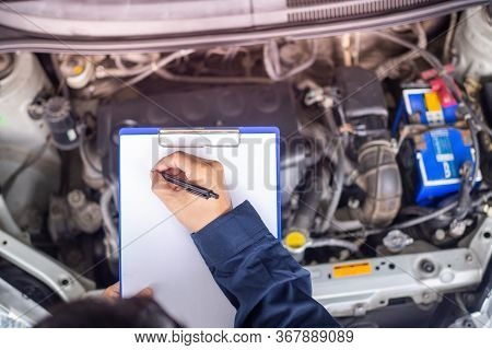 Hands Of Young Professional Mechanic In Uniform Writing On Clipboard Against Car In Open Hood At The