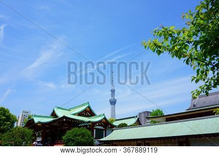 Tokyo / Japan - May 05, 2019: Kameido Tenjin Shrine. Towers Behind The Shrine. Blue Sky