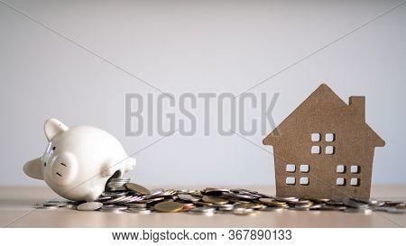 White Pig Piggy Bank With Many Coins Saving Money For Building A House. There Is A New Home. The Con