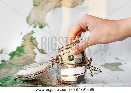 Collecting Money For Travel. Hand With Coin, Money Box With Dollar Banknotes. Cash Savings In Glass