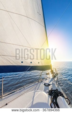Sailing with sun. A view from the yacht's deck to the bow and sails. Sail boat with set up sails gliding in open sea. Greece, Europe