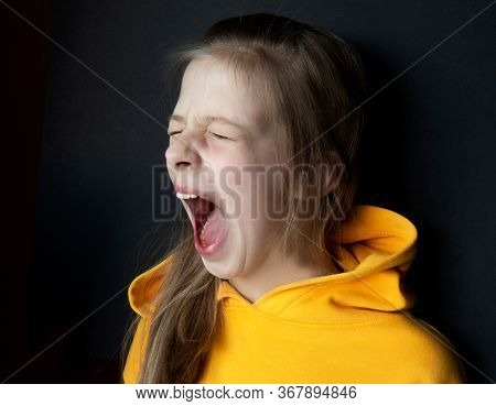 Teenager Girl In An Orange Sweatshirt With Bright Emotions On Her Face On A Black Background. Girl S