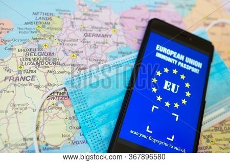 Immunity Passport App And Medical Mask On Europe Map. Travel During Covid-19 Concept.