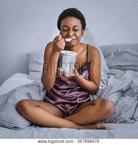Breakup And Sadness Concept. Crying African American Girl Eating Ice Cream In Bed At Home