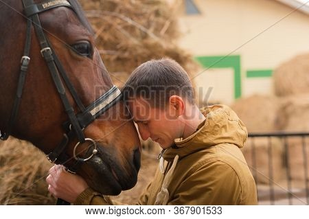 Animal. Young Handsome Man Hugs His Loving Horse And Friend. Beautiful Warm Autumn Day. Outdoor. Nat
