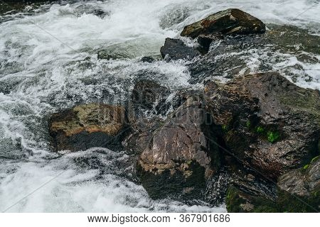 Big Stones With Moss And Lichen In Water Riffle Of Mountain River. Powerful Water Stream Of Mountain
