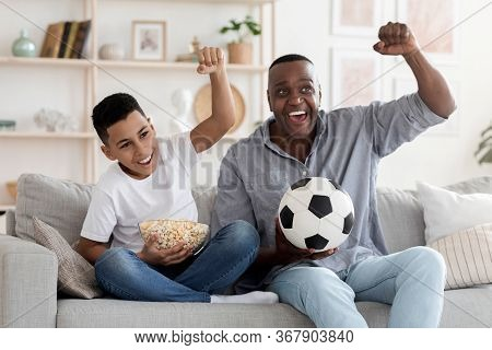 Joyful African Grandfather And Hid Grandson Cheering While Watching Football On Tv In Living Room At