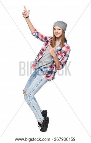 Teen Girl Standing In Full Length On Tiptoe Pointing To Side At Blank Copy Space