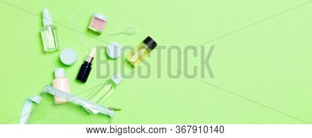 Group Of Small Bottles For Travelling On Green Background. Copy Space For Your Ideas. Flat Lay Compo
