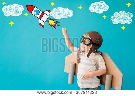 Happy Child Playing With Toy Paper Wings Against Blue Background. Kid Having Fun At Home. Imaginatio