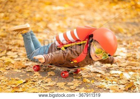 Happy Child Having Fun Outdoor In Autumn Park