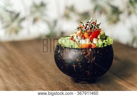 Poke Bowl With Tuna, Avocado, Vegetables And Sesame In Coconat Bowl On Pattern Background. Healthy,