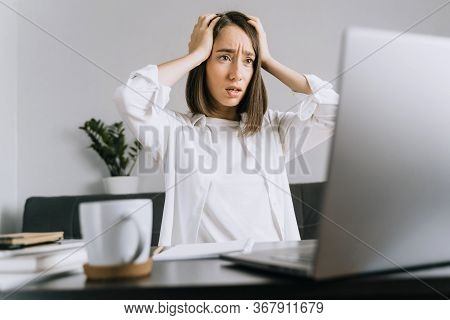 Tired And Shocked Young Business Woman Or Student With A Headache Using Laptop And Looking At The Sc