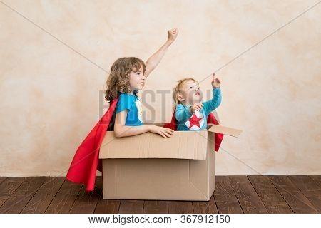 Superheroes Children Playing In Cardboard Box. Kids Having Fun At Home. Childhood Dream And Imaginat