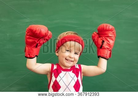 Funny Child Student Wearing Red Boxing Gloves In Class. Happy Kid Against Green Chalkboard. Physical