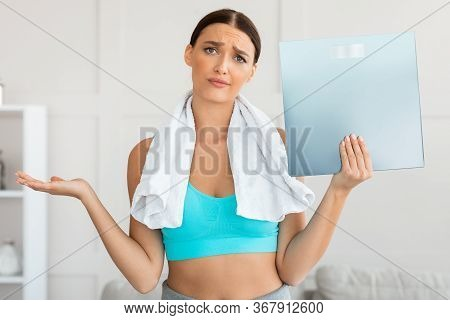 Discontented Girl Holding Weight Scales Not Losing Kilograms On Unsuccessful Diet Standing At Home.
