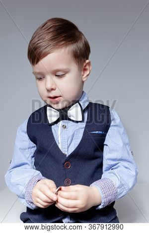 A Boy In A Shirt, Bow Tie, Vest And Trousers On A White Background Holds Coins In His Hands. Stylish