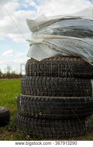 Environmental Pollution. Garbage Dump In The Field. Illegal Garbage Dump. Abandoned Old Tires