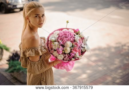 Beautiful Blonde Girl Holds Magnificent Bouquet Of Flowers And Looks At Camera.
