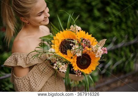 Smiling Woman Accurate Holds Bouquet With Sunflowers In Her Hands.