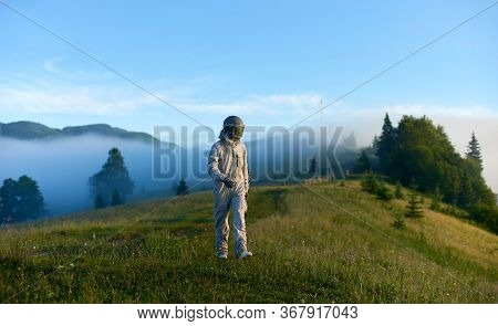 Astronaut Wearing White Space Suit And Helmet Walking Alone Sunny Green Mountain Glade In The Mornin