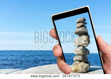 Stone Tower On Smartphone Screen. Folded Balancing Stick, Folded With Precision. Copy Space.