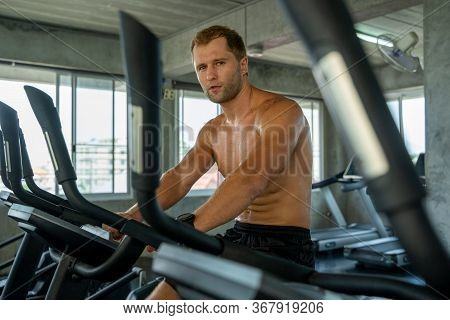 Fitness Man Running On Modern Electric Treadmills At The Gym,man On Electric Treadmills.