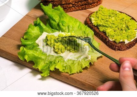 Preparation Of Avocado Puree Sandwiches. A Woman Puts Avocado Puree On A Lettuce Leaf With A Fork. B