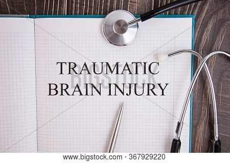 Notebook Page With Text Traumatic Brain Injury, On A Table With A Stethoscope And Pen, Medical Conce