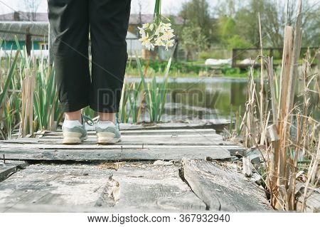 Girl Stands On An Old Wooden Bridge On A Pond With A Bouquet Of Daffodils