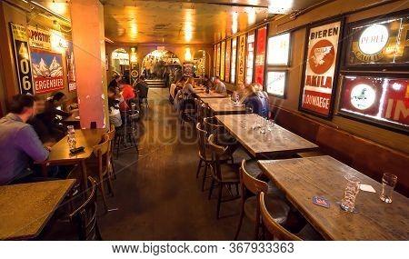 Brussels, Belgium: Historical Belgian Bar With Customers, People Meeting And Drinking Beer Inside Vi